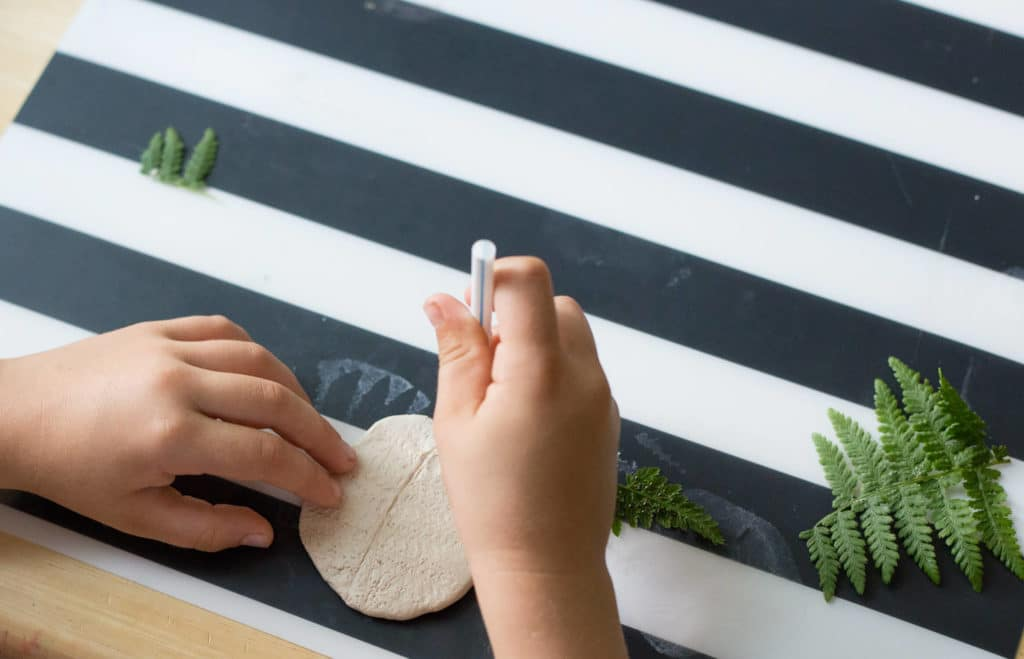 Add a hole at the top of your clay leaf print with a straw