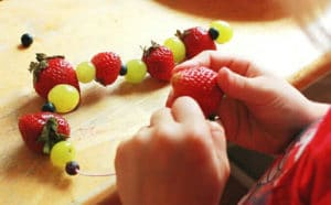 Fruit Necklaces Make a Fun Kids Snack - threading fruit necklace