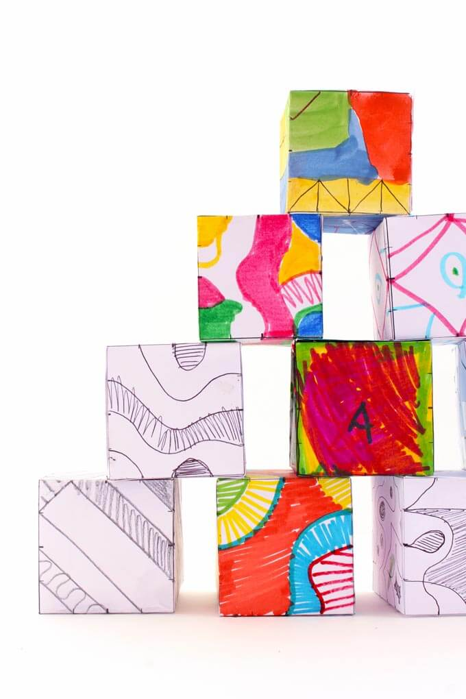 Finished colorful doodle cubes stacked up together.