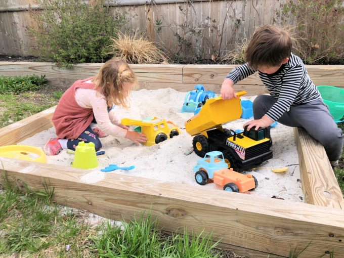 Children playing in sandbox for kid friendly backyard