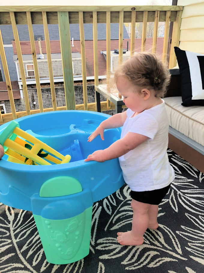 baby playing at a water table