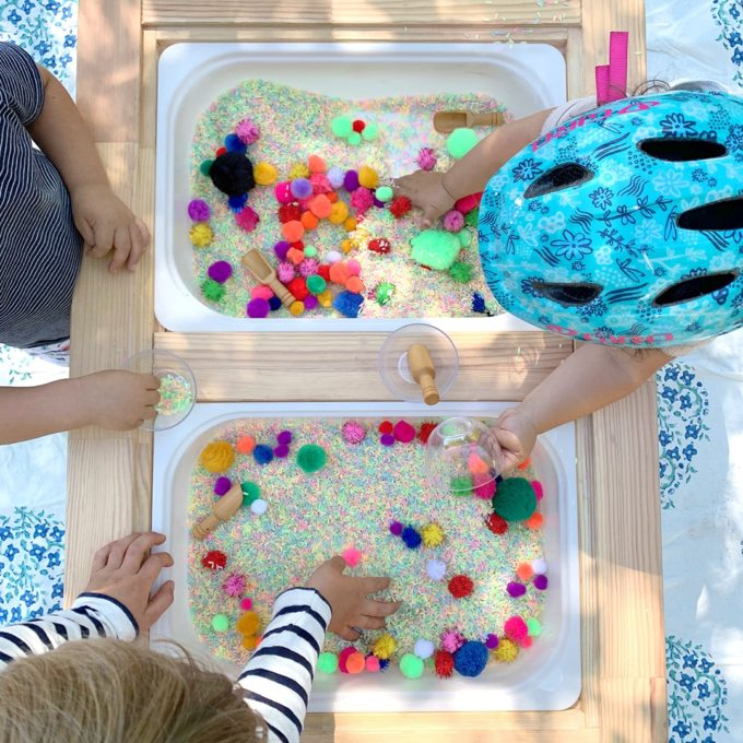 Kids playing at rice table with pom poms