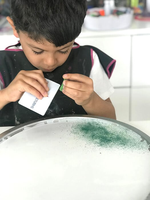 Scraping chalk pastels with a plastic card for an easy chalk art activity.