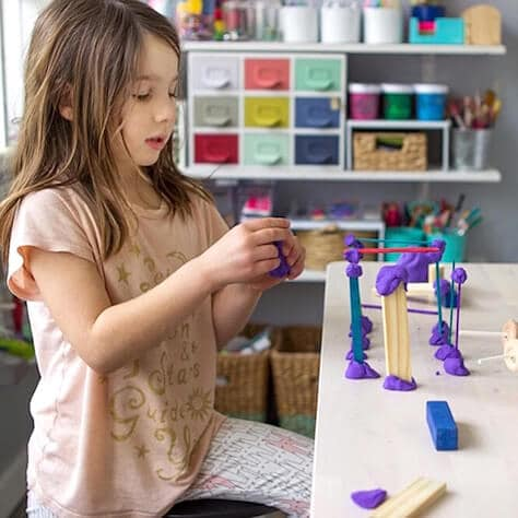 Girl creating sculpture project with wood & playdough in art space