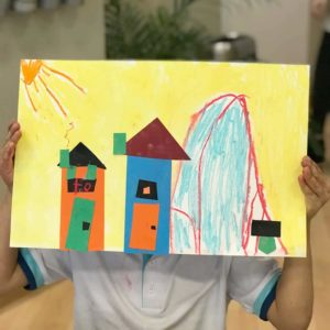 Boy holding up mixed media collage art idea – Paul Klee inspired city art