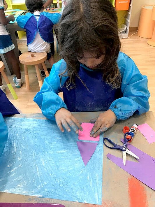 Girl glueing shapes on paper for city mixed media project – Paul Klee Art for Kids