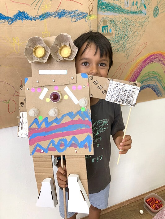 Boy holding large cardboard robot puppet made with recycled materials