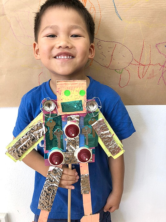 Boy holding painted cardboard robot puppet