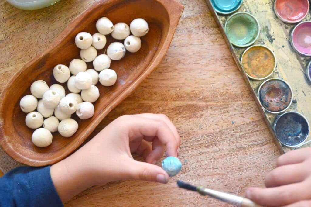 Child painting clay beads for nature mobile