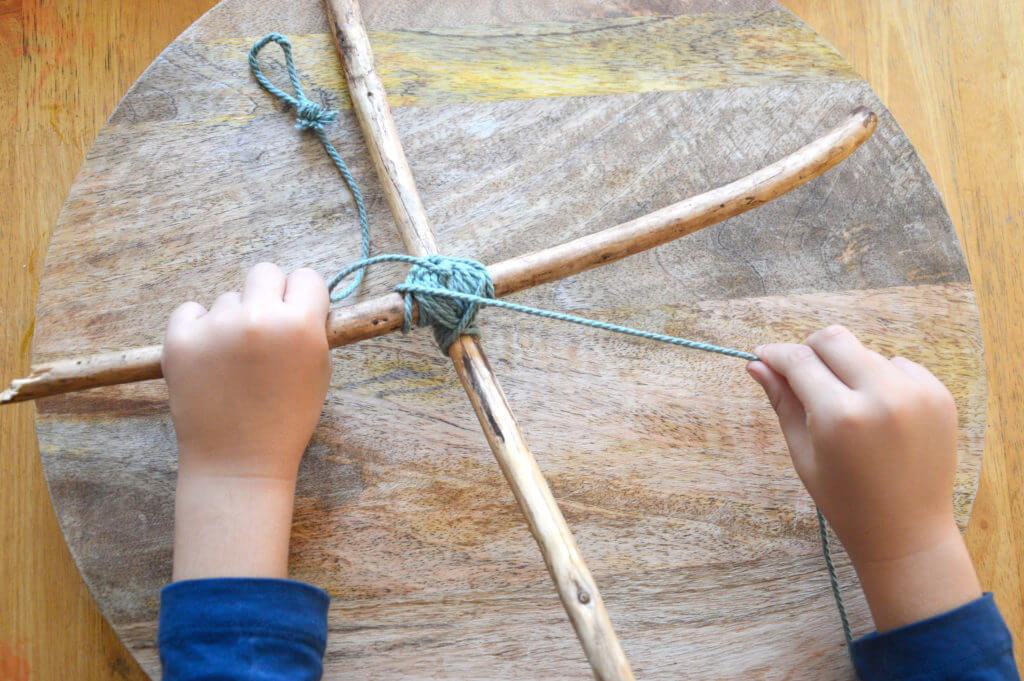 Child winding cord around sticks in x shape for nature mobile