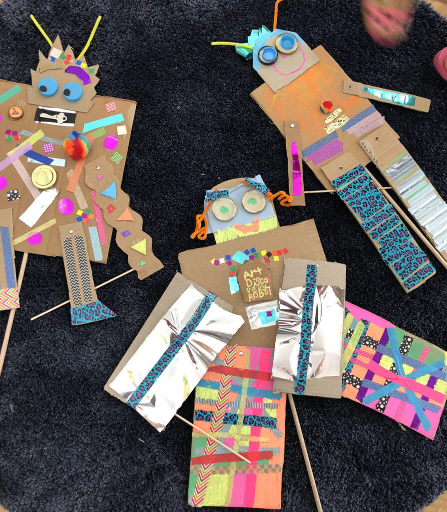 Three colorful cardboard robot puppets