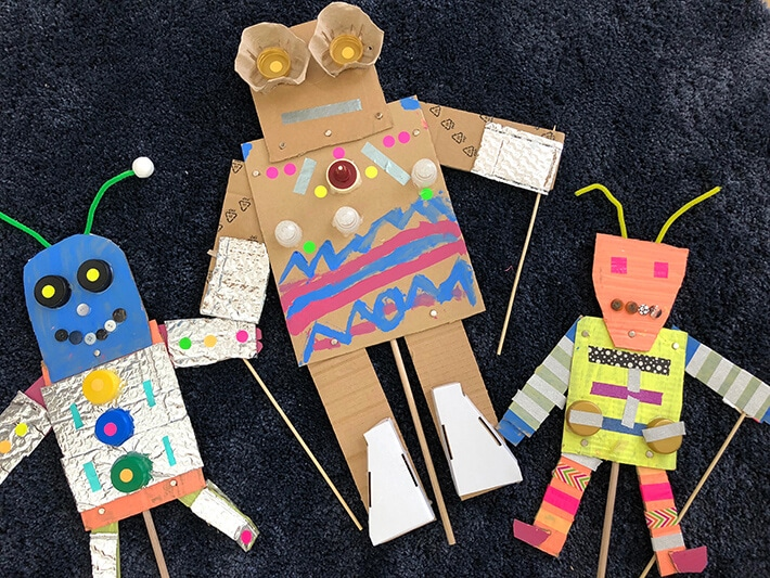 Three colorful robot puppets made with cardboard and other recycled materials