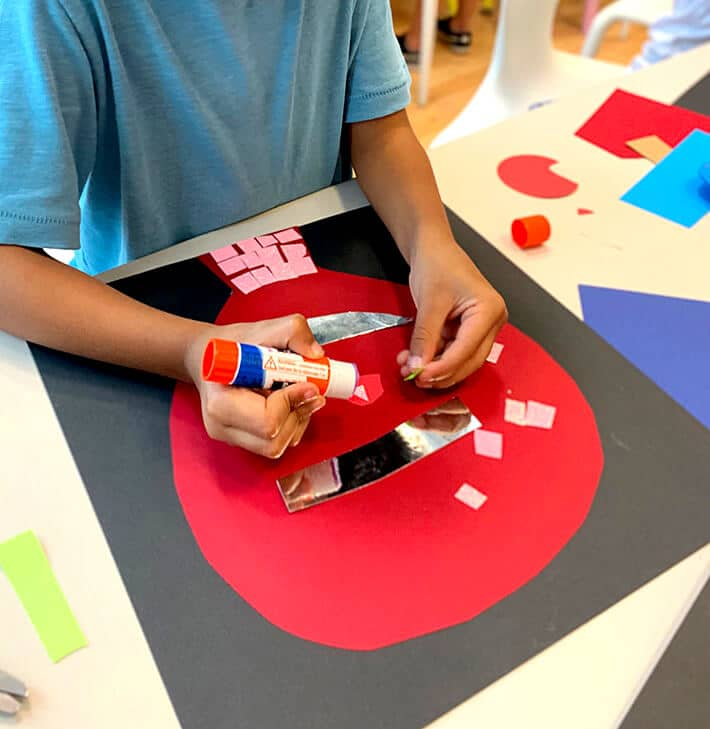 Student creating Picasso collages and self portrait for kids with cut paper shapes