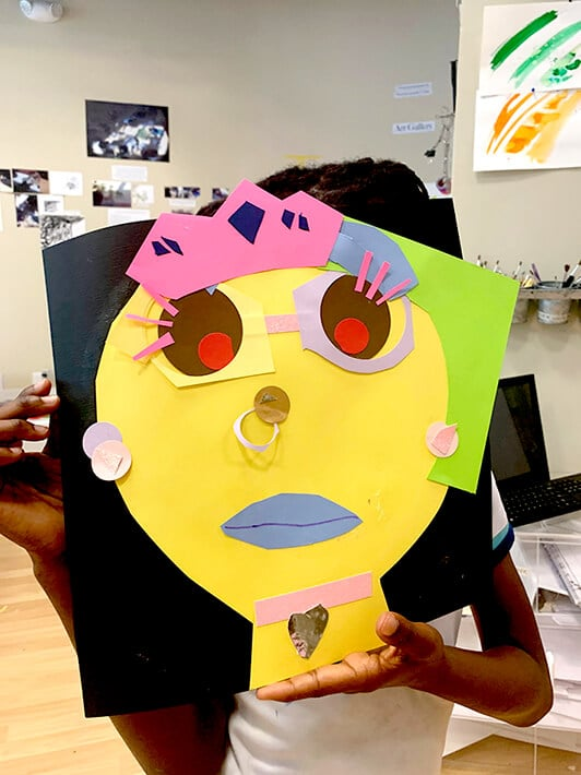 Student holds up self portrait inspired by Pablo Picasso
