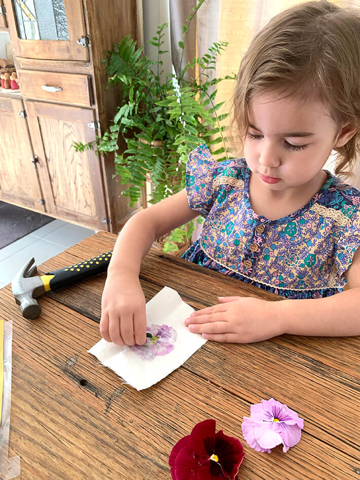 Child peeling off flower from flower flag with hammer and flowers at table