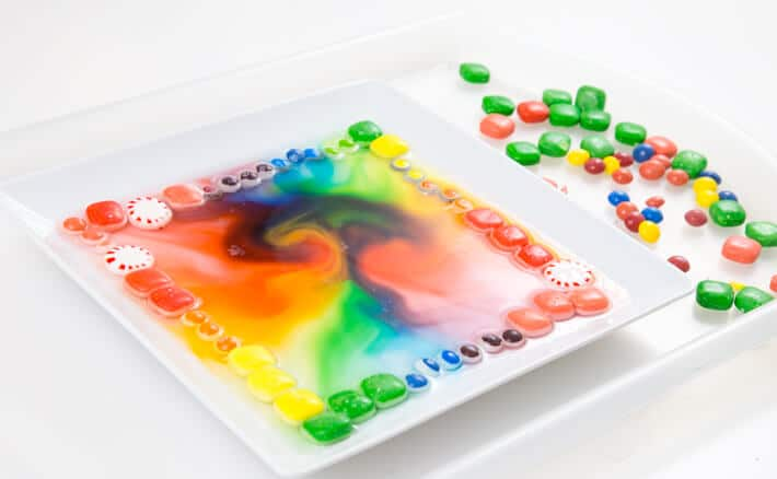 Dissolving Candy Art with a Variety of Candies around the perimeter of a square plate