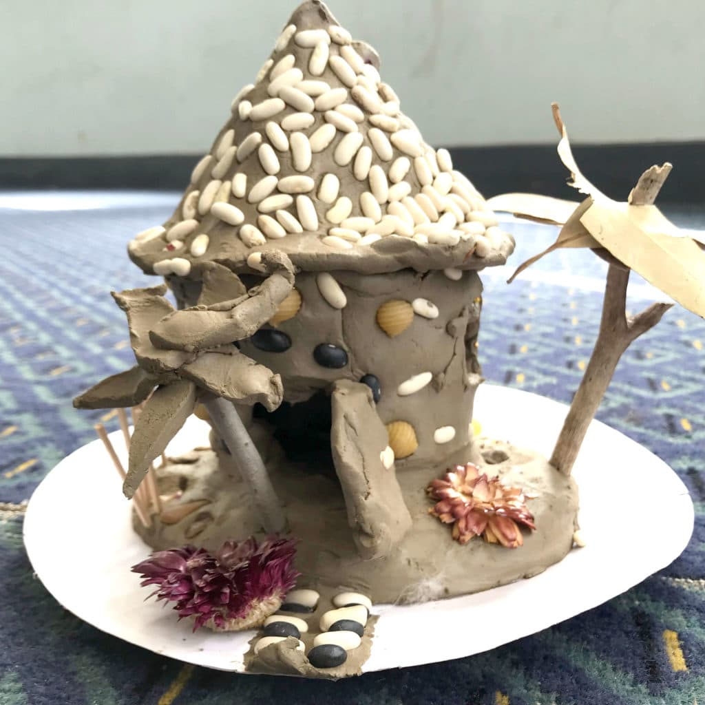 A clay fairy house with beans and pasta details
