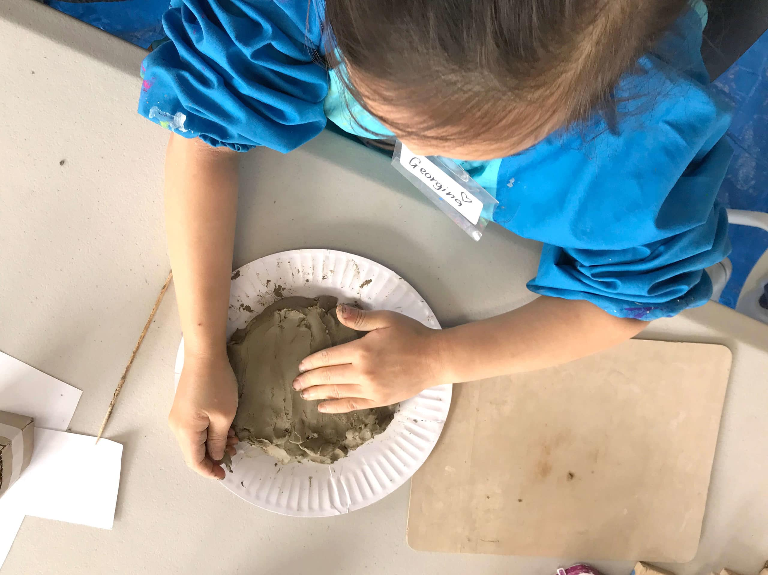 Child flattening clay on paper plate for fairy house base