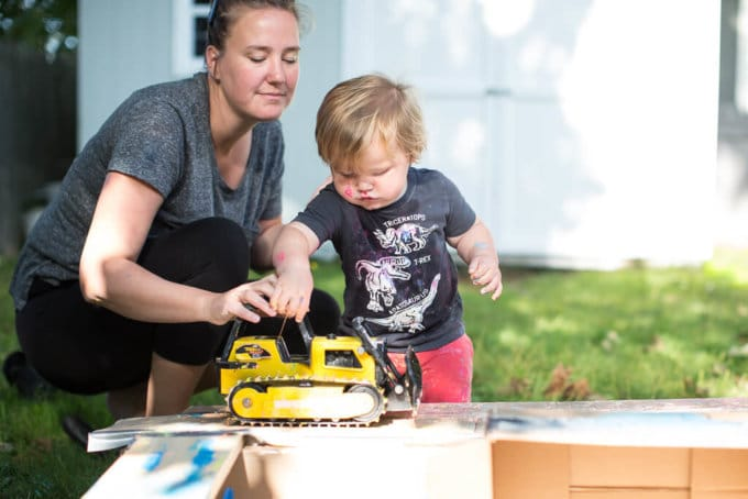 A boy pushing a bulldozer on a cardboard box for a wheel painting art activity