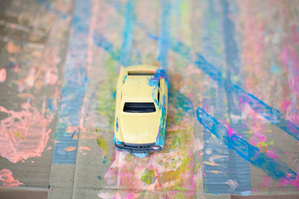 A yellow car on cardboard with tracks from painting with wheels
