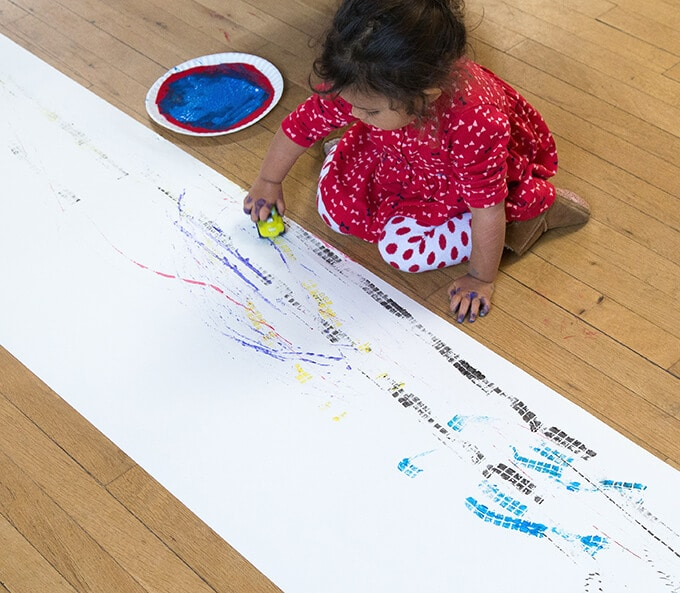 Girl making tracks with a car and paint on a roll of paper