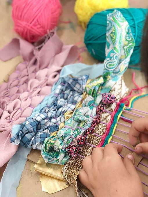Student weaving yarn and ribbon on cardboard loom