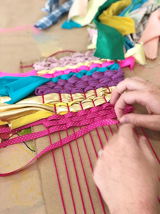 Weaving for kids with ribbon and yarn on a cardboard loom