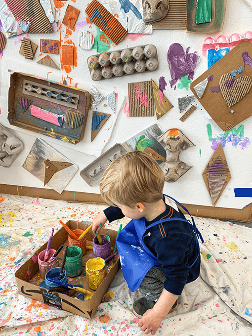 Child painting at recycled cardboard collage wall at kids art studio