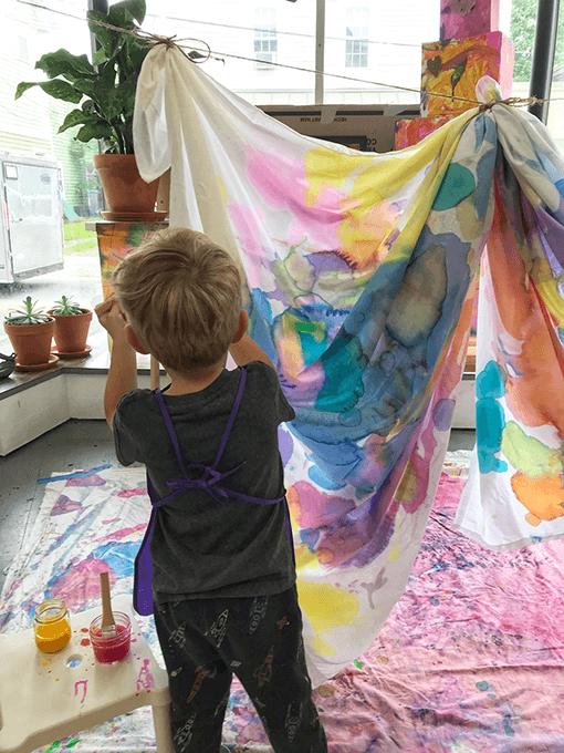 Child painting white sheet with liquid watercolors in kids art studio