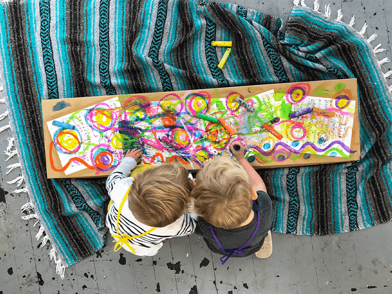 Two children painting with tempera paint sticks on sheet music