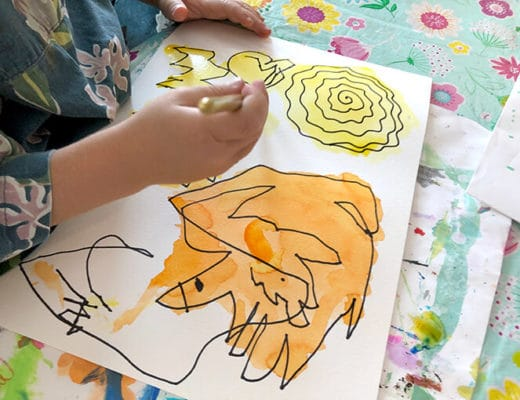 Child drawing on a watercolor painting