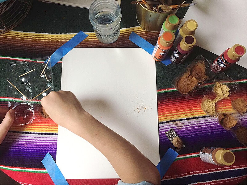 Child painting with spices and paint