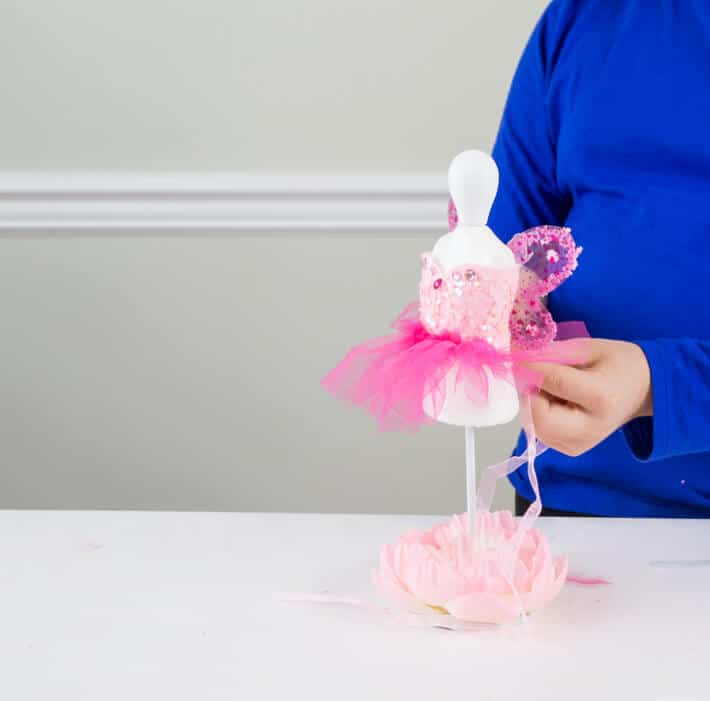 Child making a tiny tutu for a fairy doll