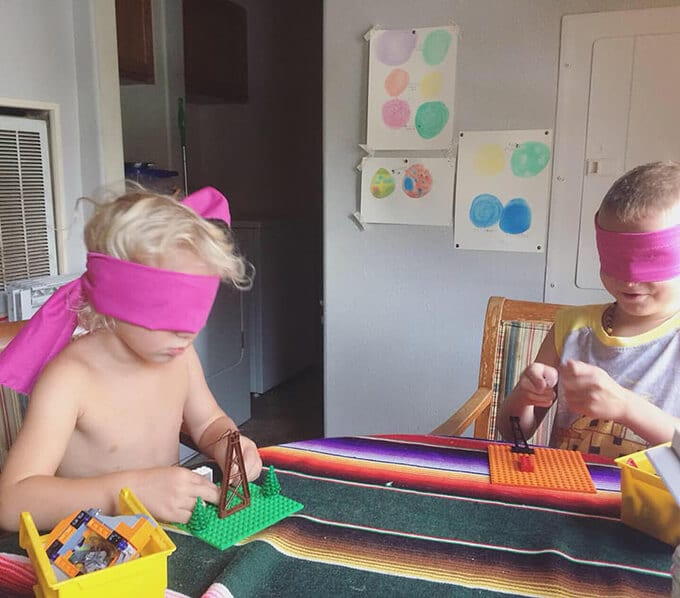 Two children building LEGOs while blindfolded