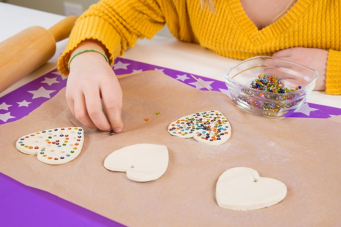 Child decorating air dry clay heart ornaments with beads