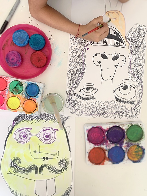 Child painting with watercolor portraits during family drawing game