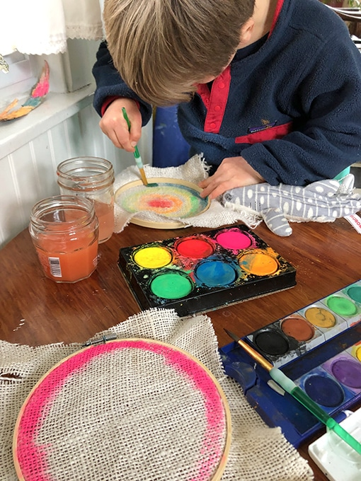 Child painting burlap in embroidery hoop for stitching project for kids