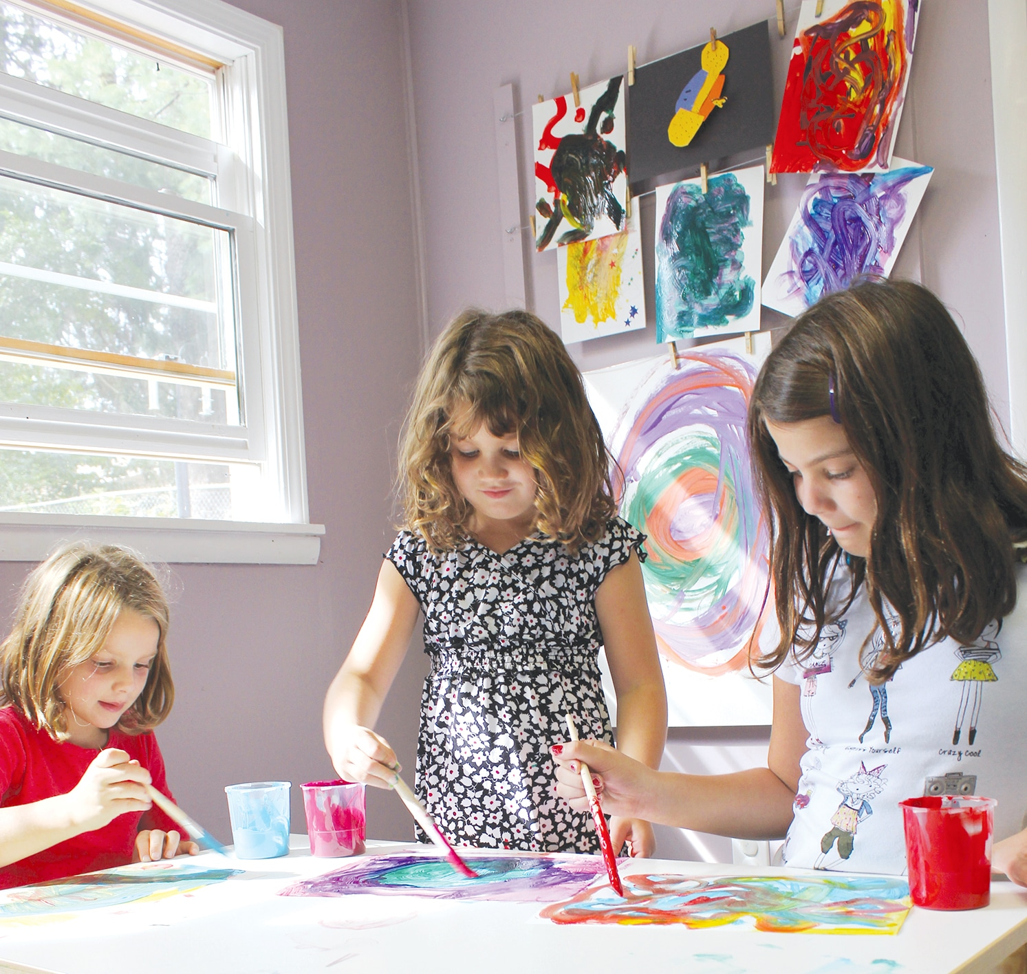 Girls painting at table with art hanging in background.