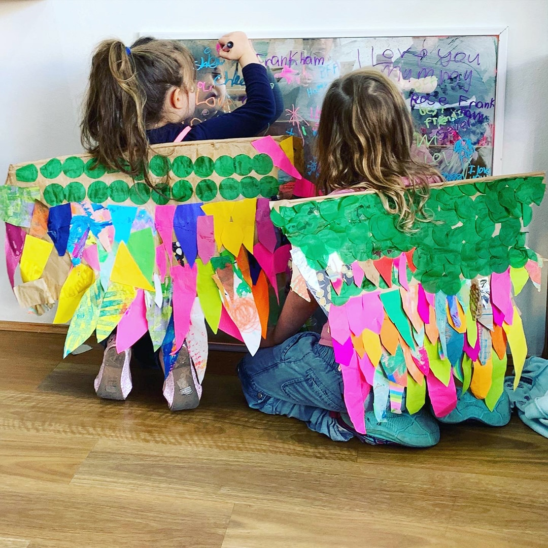 Two girls with wearing brightly colored DIY paper wings