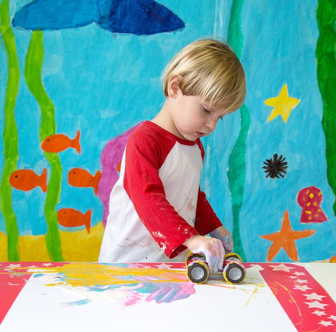 Child-painting-tracks-with-car