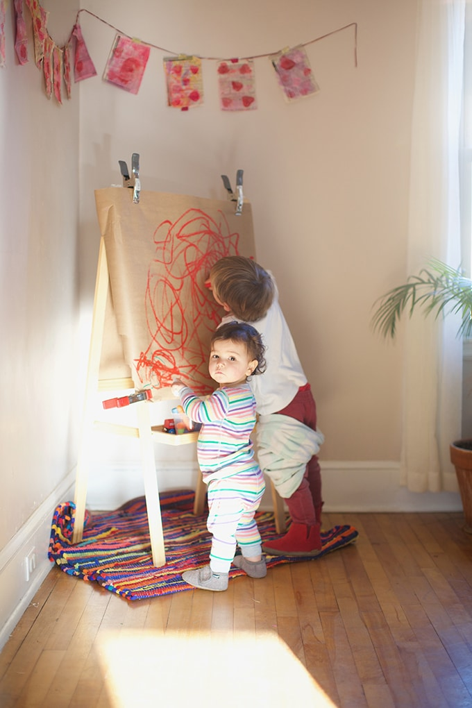 Children painting at easel with paint sticks - Rachel Withers