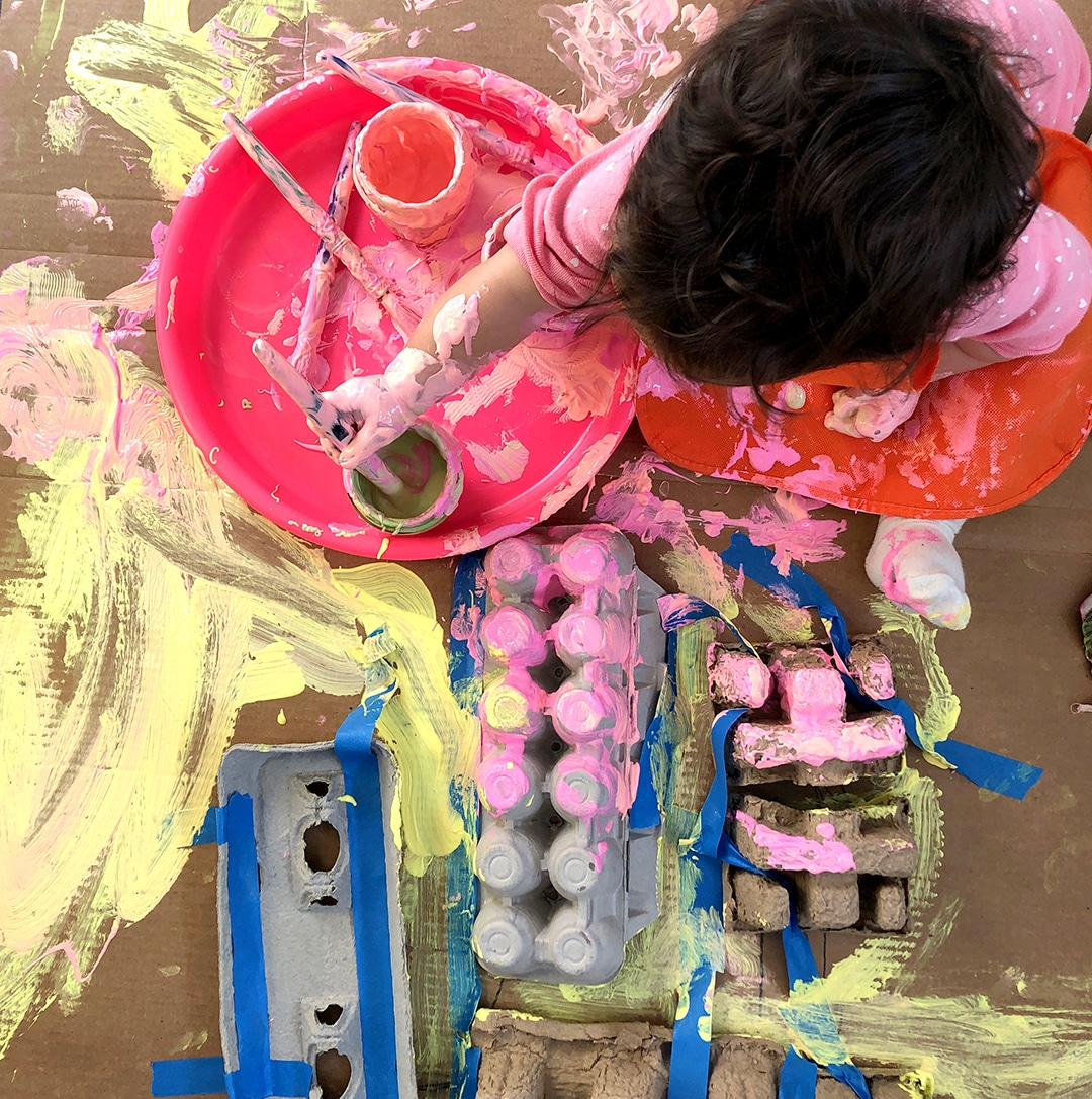Toddler painting pieces of recycling and cardboard_Rachel Withers