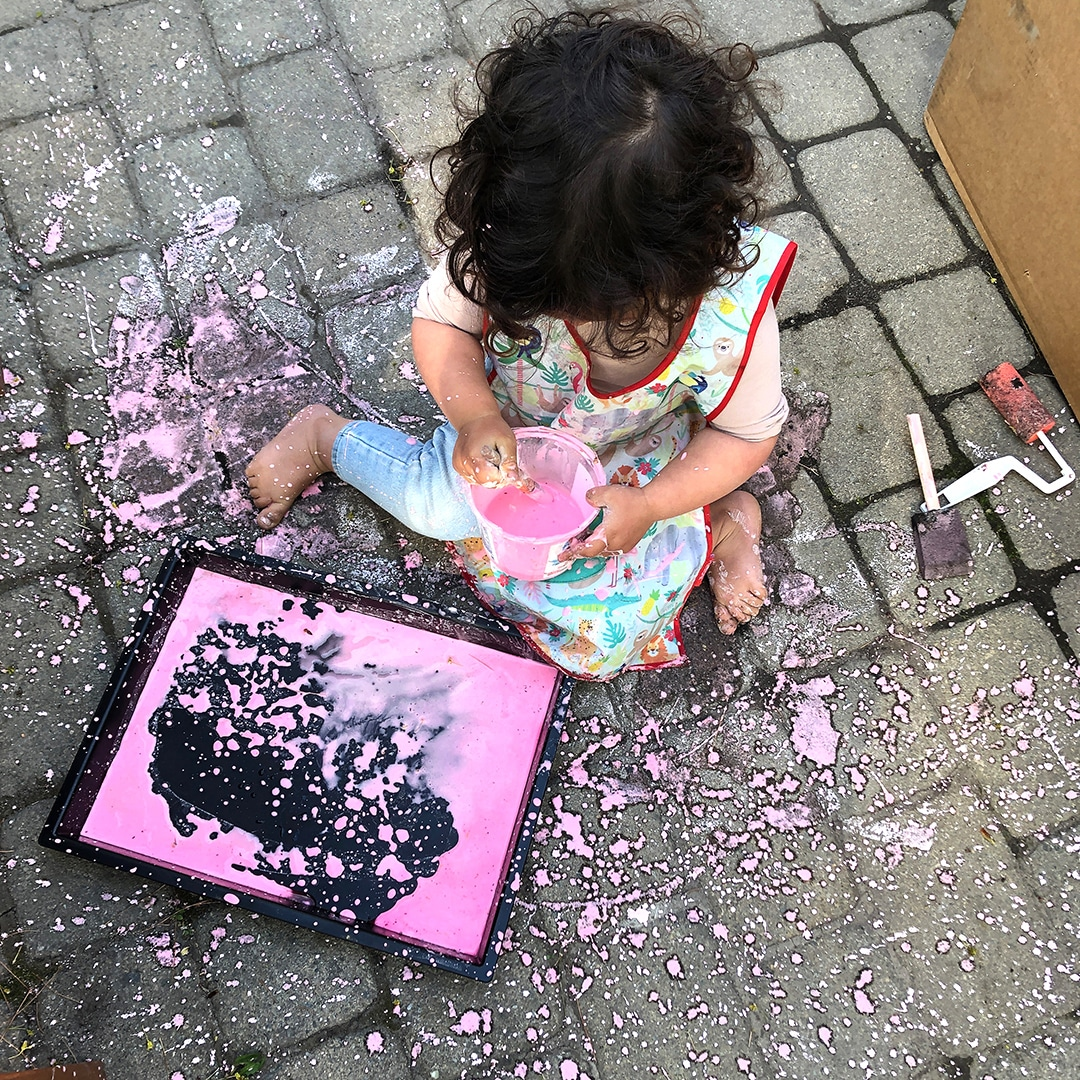 Child painting with sidewalk paint