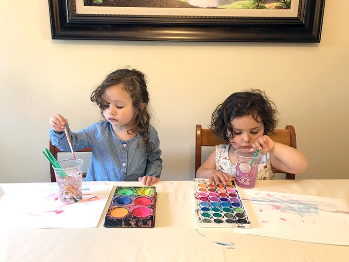 Toddlers painting with watercolors on paper. Photo by Rachel Withers